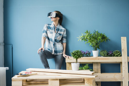 Woman using VR glasses, renovating her new home - MOEF00876