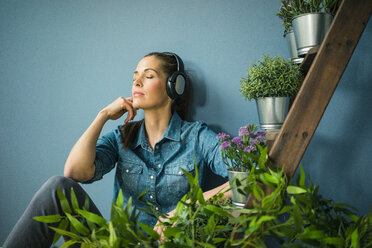 Beautiful woman in her home, decorated with plants, listening music with headphones - MOEF00879