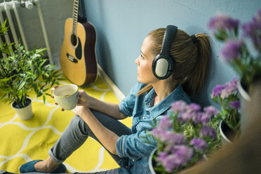 Beautiful woman in her home, decorated with plants, listening music with headphones - MOEF00882