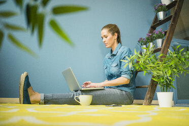 Beautiful woman in her home, decorated with plants, using laptop - MOEF00885