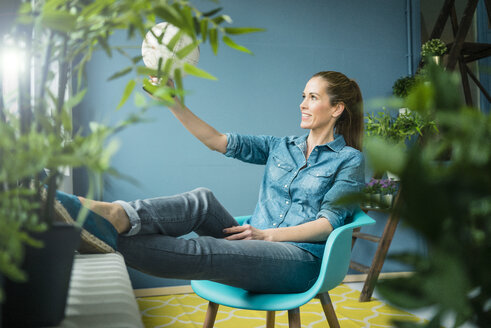 Beautiful woman sitting in her home, decorated with plants, looking at globe - MOEF00888