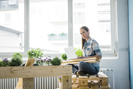 Woman refurbishing her new home with pallets, using laptop - MOEF00894