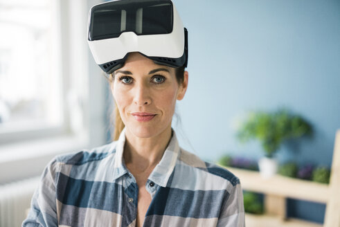 Woman using VR glasses, renovating her new home - MOEF00897