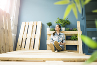 Beautiful woman taking a break from refurbishing her home with pallets, drinking coffee - MOEF00903