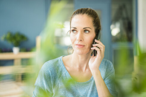 Woman talking on the phone in her new home - MOEF00909