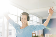 Portrait of a beautiful woman, listening music with headphones - MOEF00912