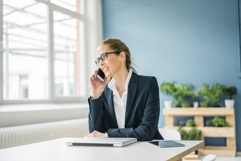 Businesswoman working from home, talking on the phone - MOEF00918