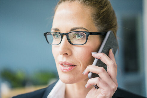 Successful businesswoman standing at home, talking on the phone - MOEF00921