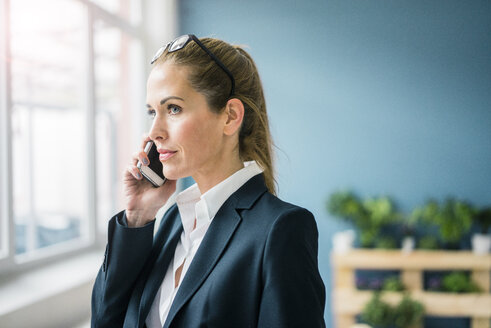 Successful businesswoman standing at home, talking on the phone - MOEF00924