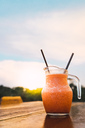 Thailand, carafe with refreshing drink on table at sunset - KKAF00879
