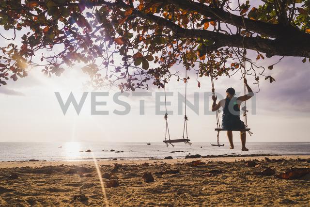 Thailand, Phi Phi Islands, Ko Phi Phi, man on tree swing on the beach at sunset - KKAF00891