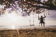 Thailand, Phi Phi Islands, Ko Phi Phi, man on tree swing on the beach at sunset - KKAF00891