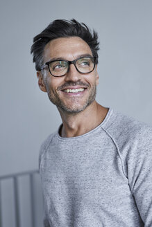 Portrait of laughing man with stubble wearing grey sweatshirt and glasses - PNEF00548
