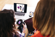 Two fashion designers with camera and laptop in studio - JRFF01581