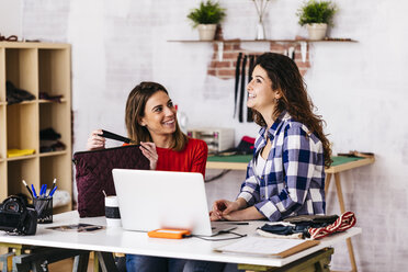Two smiling fashion designers working in studio with laptop - JRFF01584