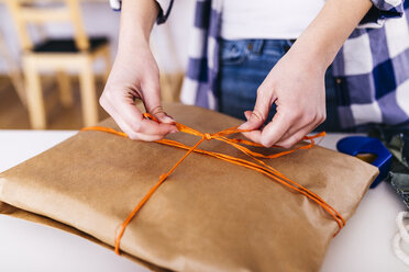 Close-up of woman wrapping a package - JRFF01599