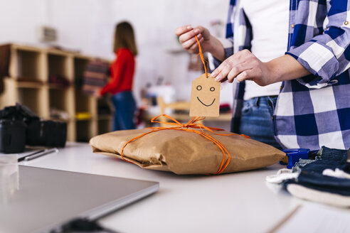 Close-up of fashion designer wrapping a package in studio with smiley face - JRFF01602