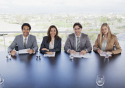 Portrait of smiling business people sitting at table in conference room - CAIF00006