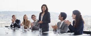 Co-workers clapping for businesswoman in conference room - CAIF00015