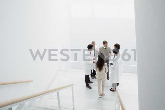 Business people and doctors on landing of stairs - CAIF00021