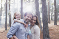 Portrait of smiling family in sunny woods - CAIF00042