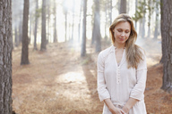 Portrait of serene woman in sunny woods - CAIF00051
