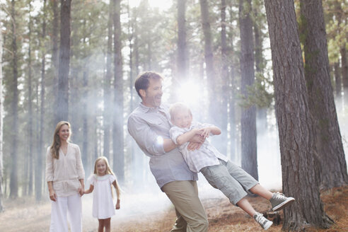 Happy family playing in sunny woods - CAIF00054