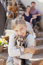 Portrait of smiling girl holding puppy with parents in background - CAIF00057