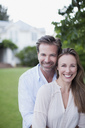 Portrait of smiling couple in yard with house in background - CAIF00060