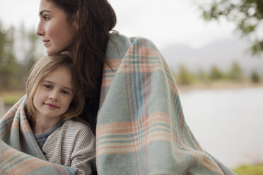 Portrait of smiling daughter wrapped in blanket with mother at lakeside - CAIF00078