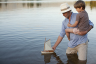 Grandfather and grandson wading in lake with toy sailboat - CAIF00090