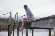 Serene woman sitting at edge of dock over lake - CAIF00093
