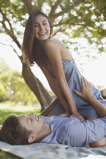 Portrait of smiling couple on blanket in grass - CAIF00111
