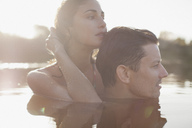 Close up of serene couple swimming in lake - CAIF00114