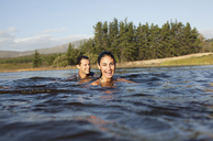 Portrait of smiling couple swimming in lake - CAIF00120