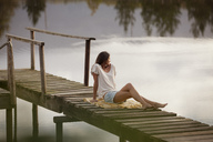 Woman sitting on dock over lake - CAIF00126
