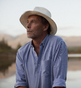 Close up of pensive man in hat at lakeside - CAIF00129