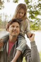 Father carrying daughter on shoulders at lakeside - CAIF00135