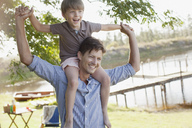 Father carrying smiling son on shoulders at lakeside - CAIF00144