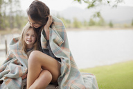 Portrait of smiling daughter wrapped in blanket with mother at lakeside - CAIF00159