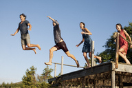 Enthusiastic friends jumping off dock - CAIF00162