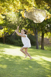 Happy girl running with butterfly net in grass - CAIF00174