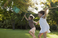 Happy boy and girl holding hands and running with butterfly nets in grass - CAIF00189