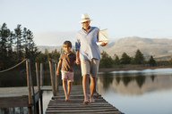 Smiling grandfather and grandson with toy sailboat holding hands and walking along dock over lake - CAIF00198