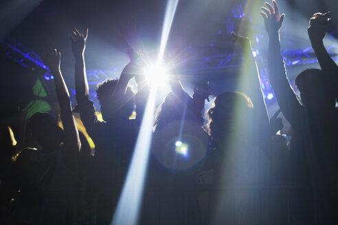 Spotlight over crowd dancing on dance floor - CAIF00204