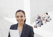 Portrait of confident businesswoman with co-workers in background - CAIF00213