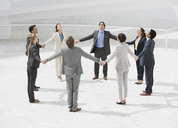 Business people holding hands in circle - CAIF00234
