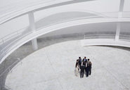 Business people standing in circle of modern courtyard - CAIF00237