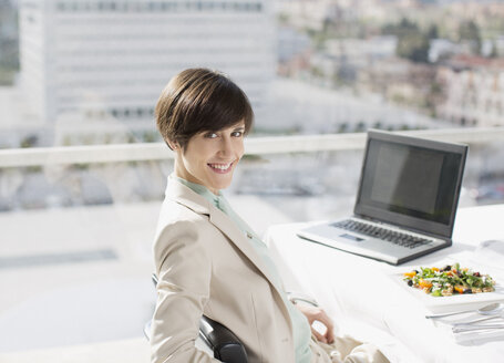 Portrait of smiling businesswoman with lunch at desk - CAIF00243
