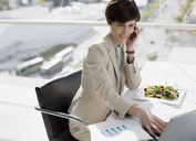 Businesswoman multitasking at desk - CAIF00249